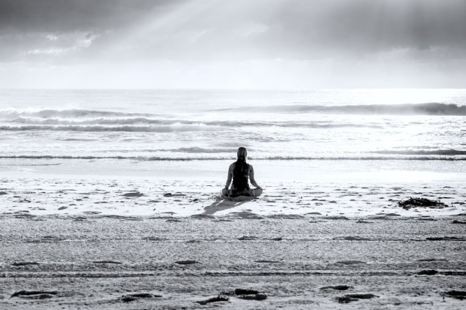 Girl meditating on beach