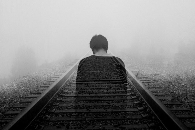A man disappearing along train tracks