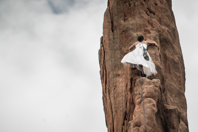 Woman climbing mountain in wedding dress
