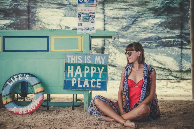 Woman sitting before sign that says 'This is my happy place'