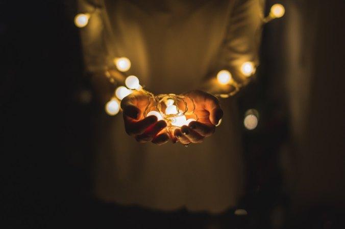 Hands holding string lights