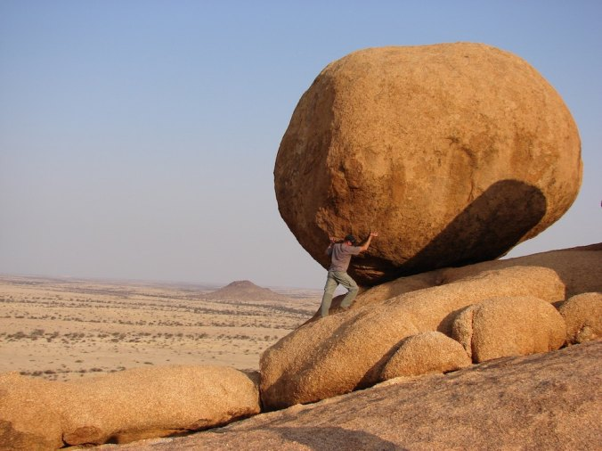 Man pushing huge boulder