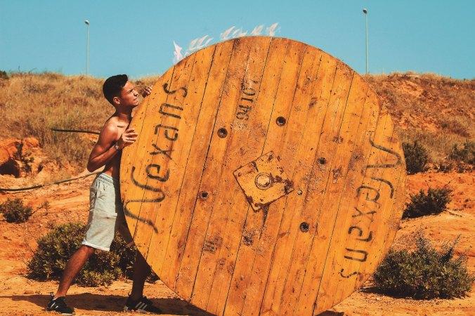 Man pushing big wooden wheel