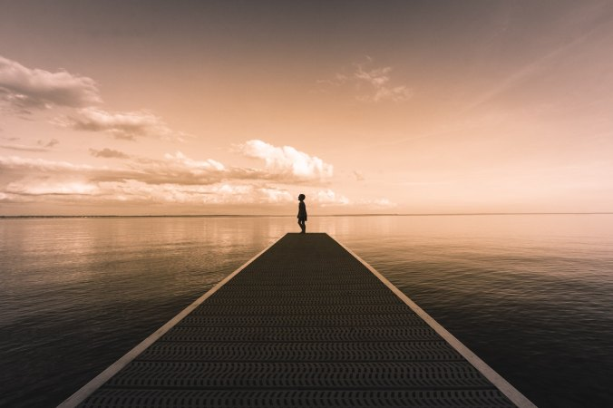 Boy at pier looking off into distance