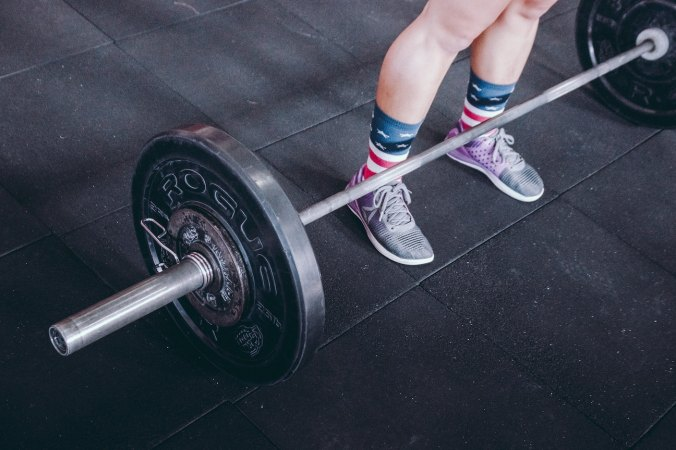 Woman standing at barbells
