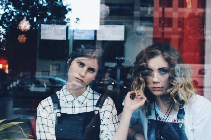 Two girls in dungarees looking bored