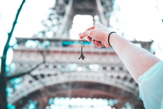 Girl holding Eiffel keychain in front of real Eiffel tower
