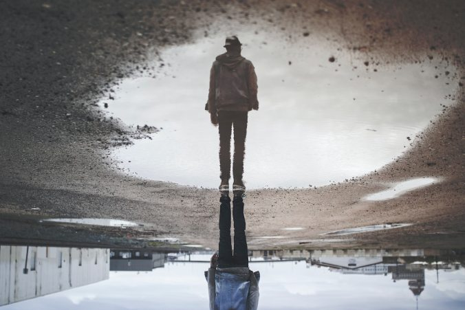 Man's photo from a reflection in a puddle