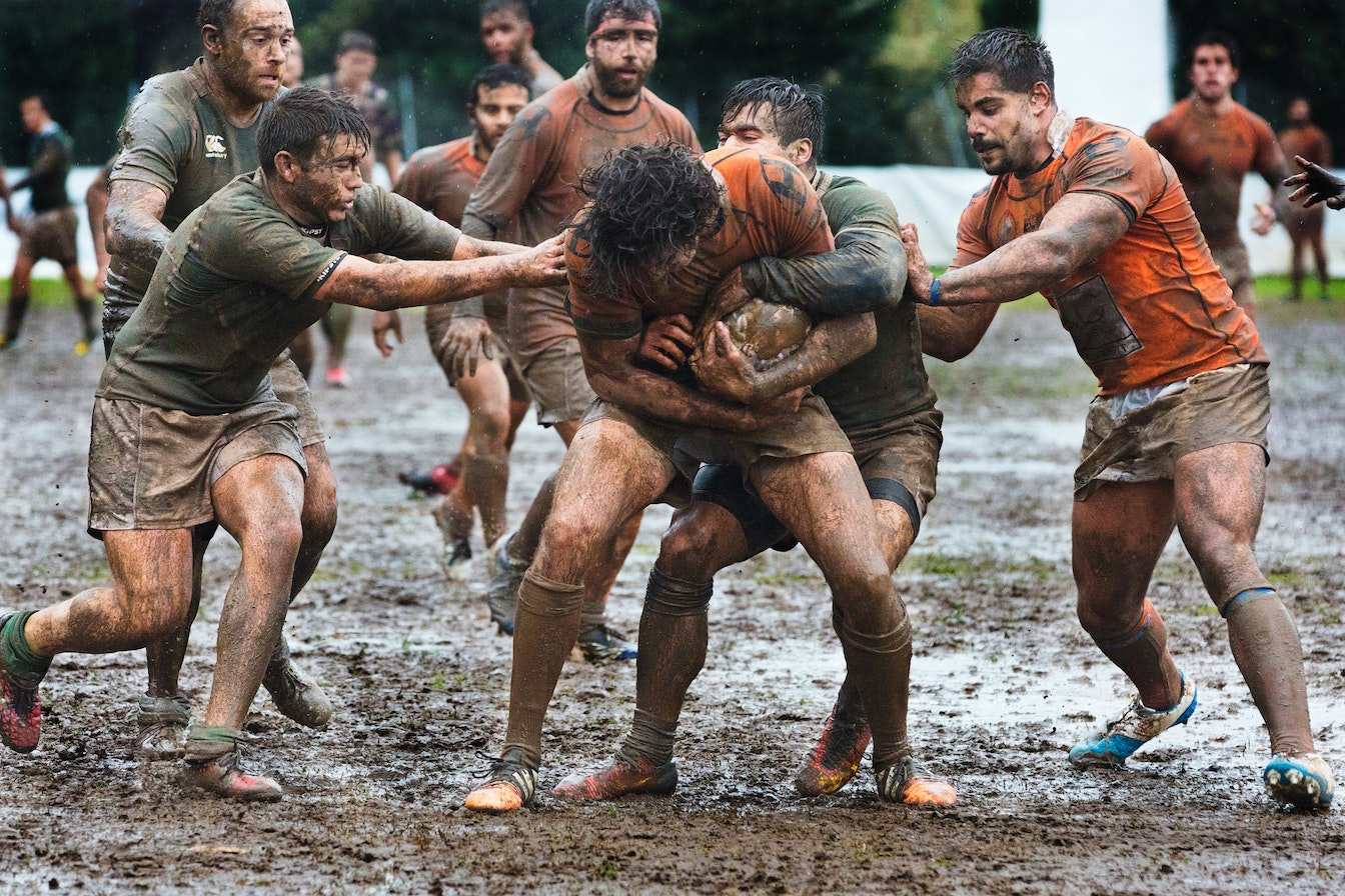 Men playing rugby in mud