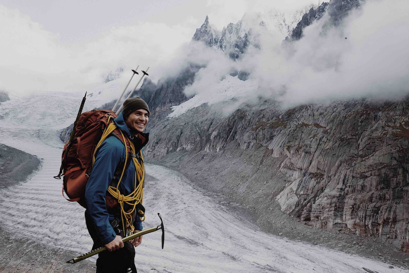 Smiling man climbing icy mountain.