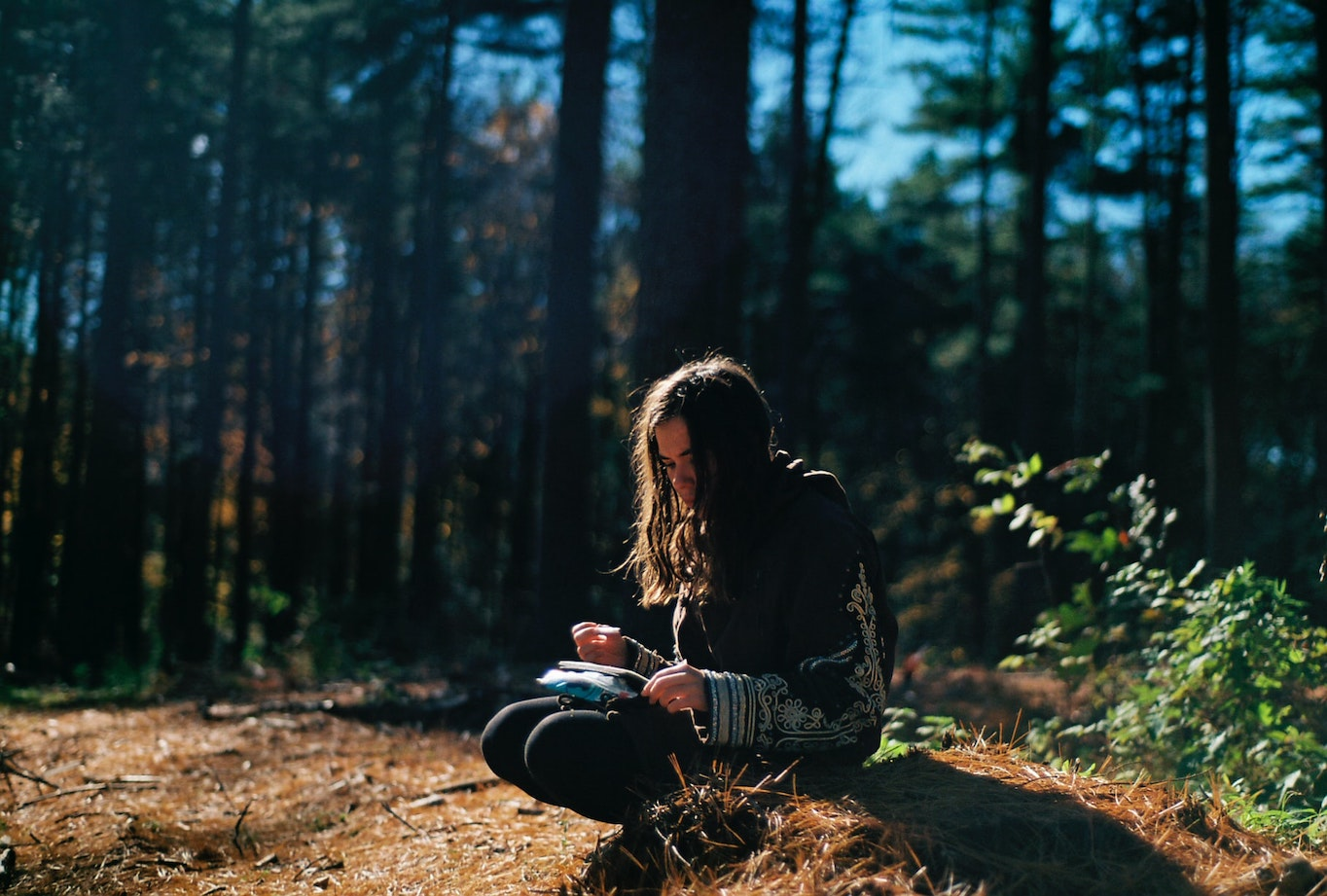 Woman writing in forest