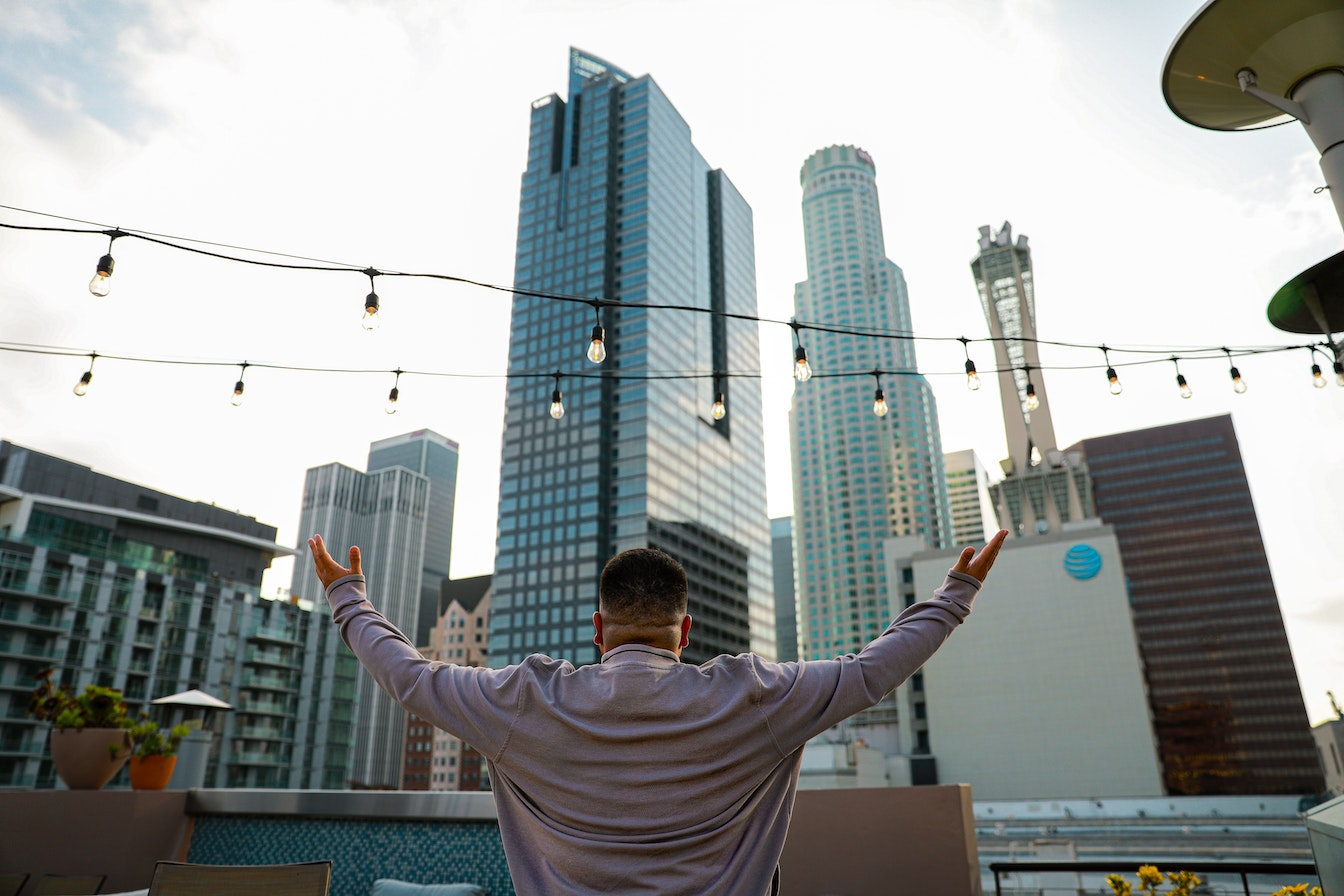 Man's arms stretched wide looking at city skyline