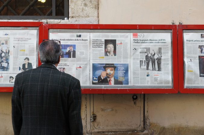 Man staring at a bunch of newspapers