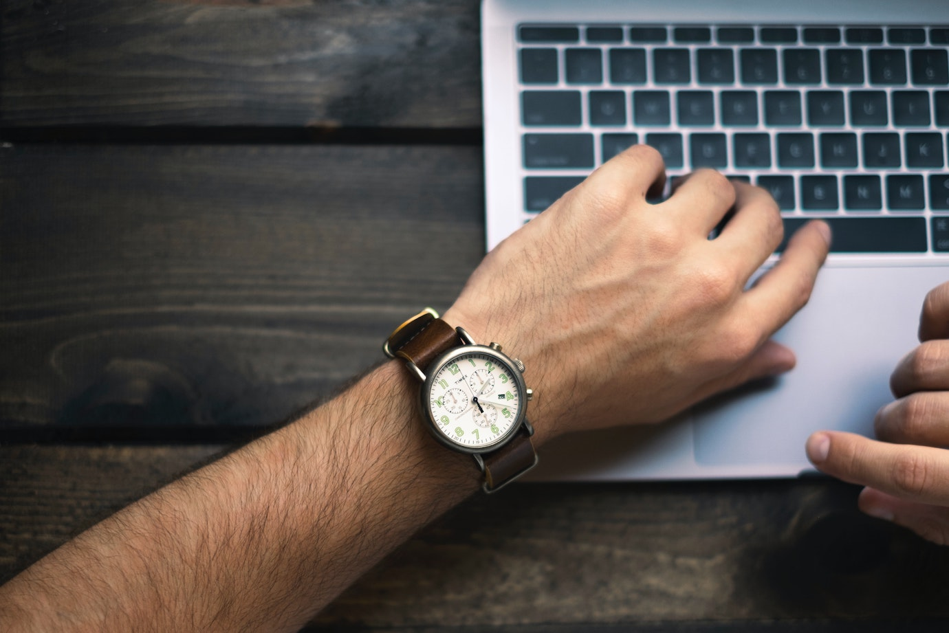 Man looking at Timex wristwatch with a laptop in the back