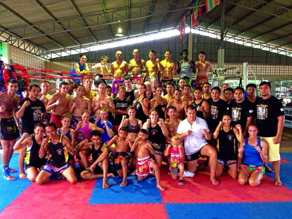 A big group of people standing in front of a Muay Thai ring