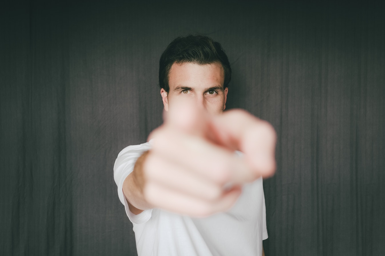 A man in a white tee pointing at the camera