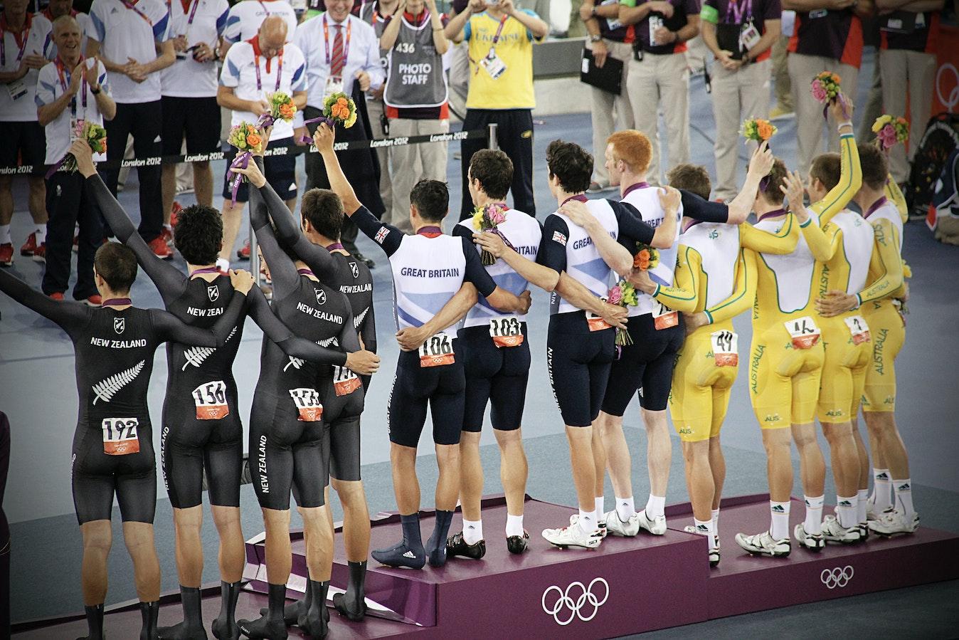 Three teams standing on an Olympics podium