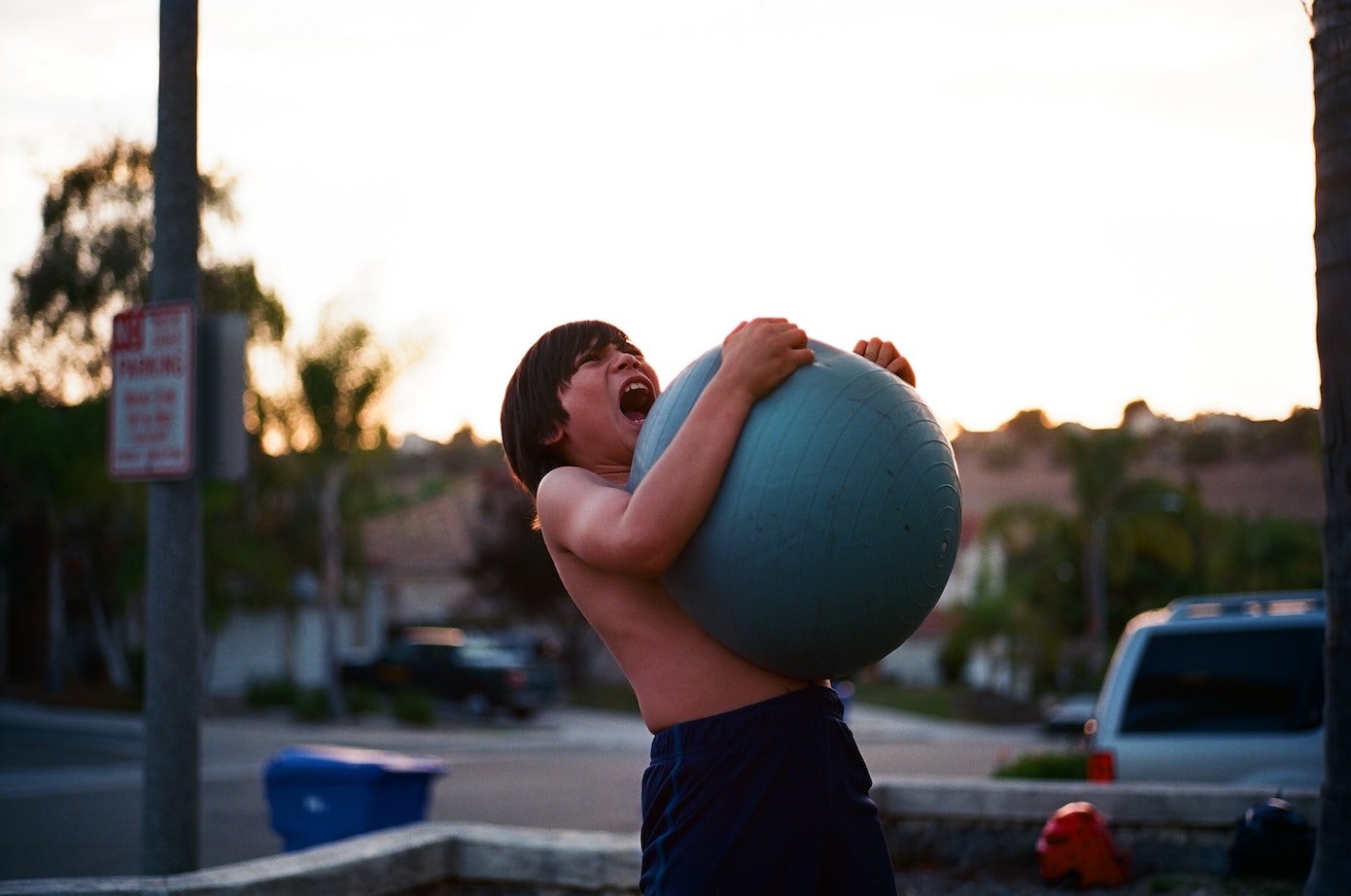 A boy grimacing while carrying a blue medicine ball