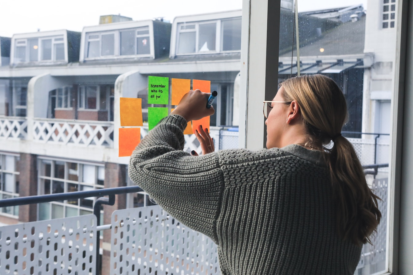 A woman writing on post-its with a marker