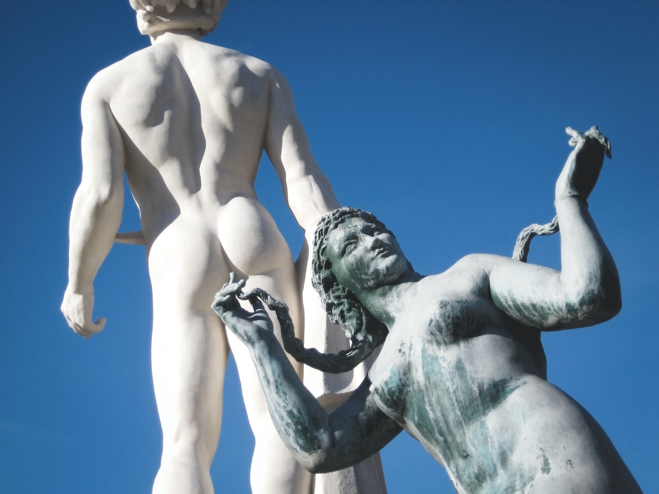 Two naked stone statues with one bum