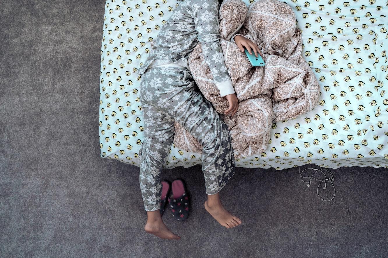 Woman lying on bed in pyjamas