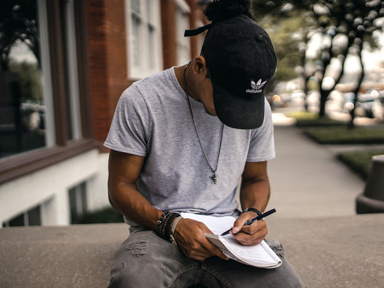 A man with a cap writing in a notebook