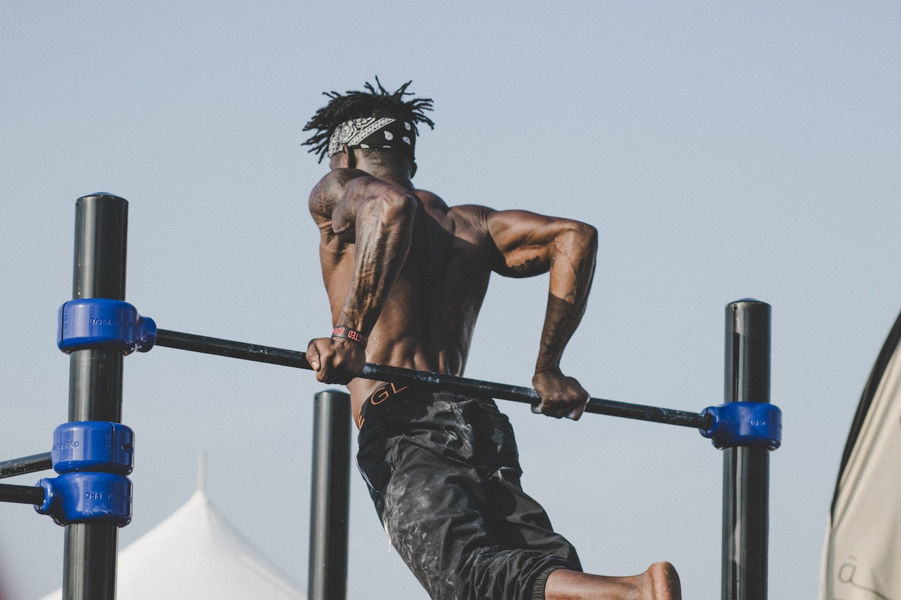 A man doing reverse dips on a bar. Photo by Kate Trysh