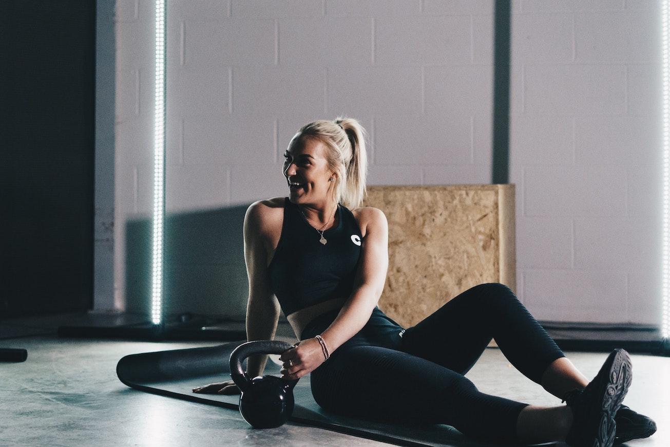Woman in sportswear sitting next to kettlebell