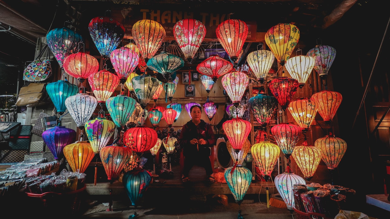 A woman standing below tens of colourful paper lanterns