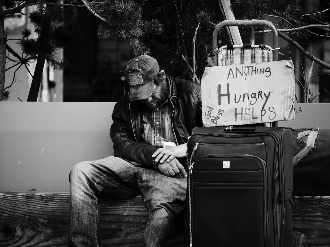 Beggar with a sign that says Hungry