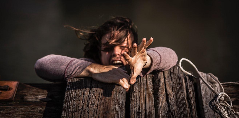 A woman falling off a wooden bridge
