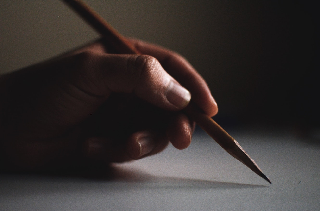 Person holding a sharp wooden pencil