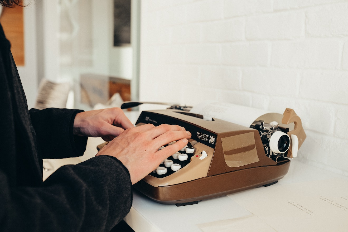 Someone typing on a brown classic typewriter