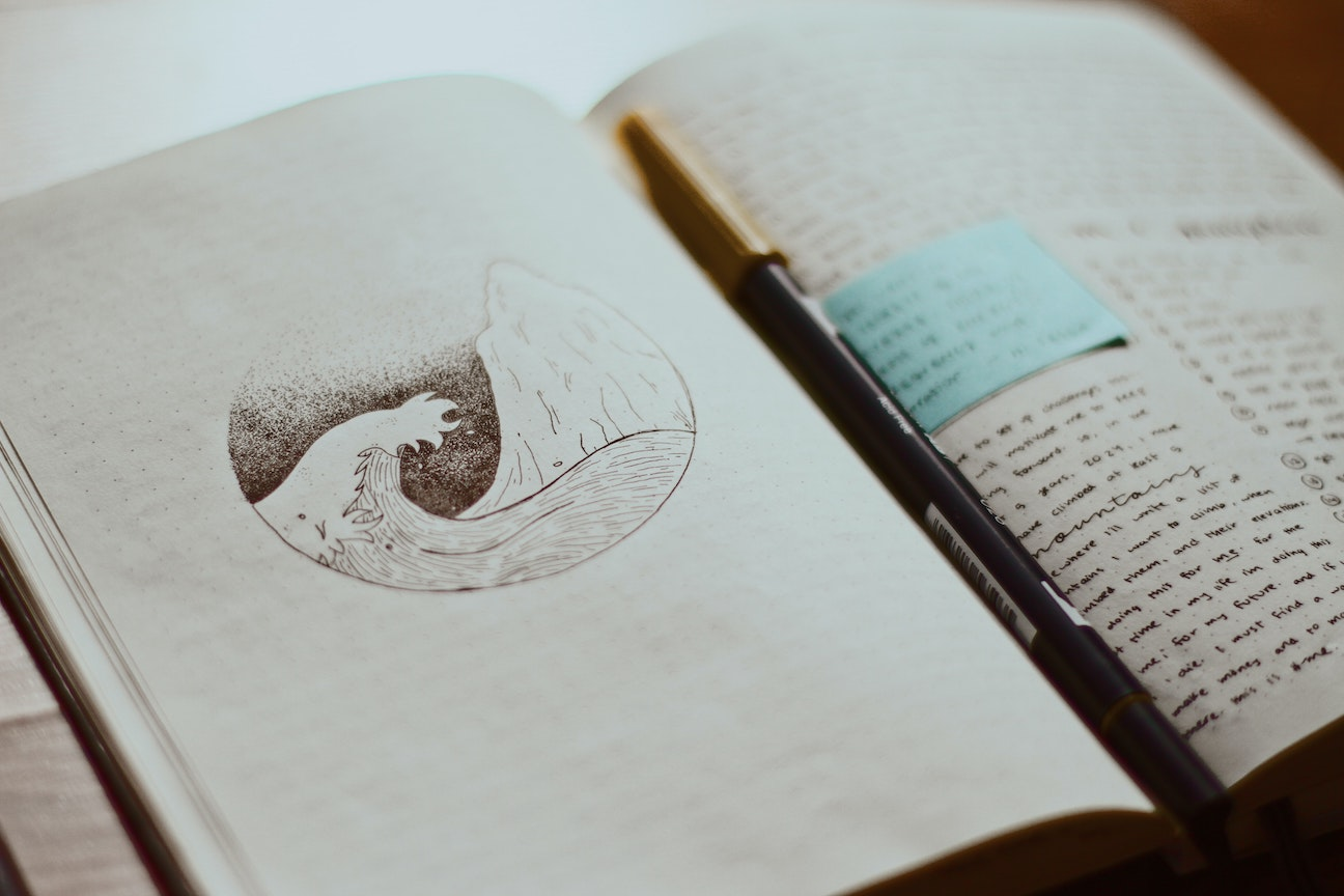 A journal spread with sketch and writing, and a pen