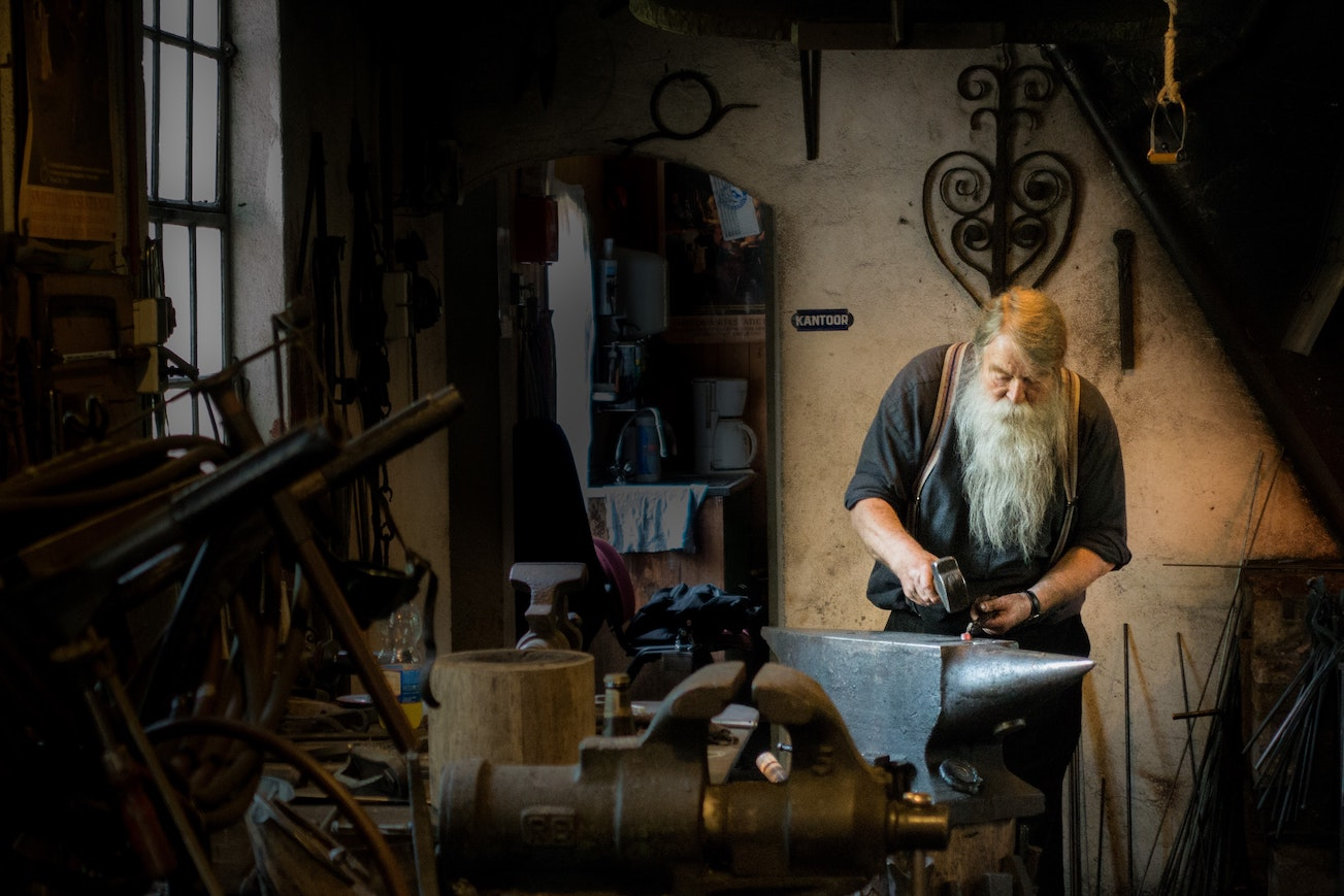 An old bearded man working at an anvil