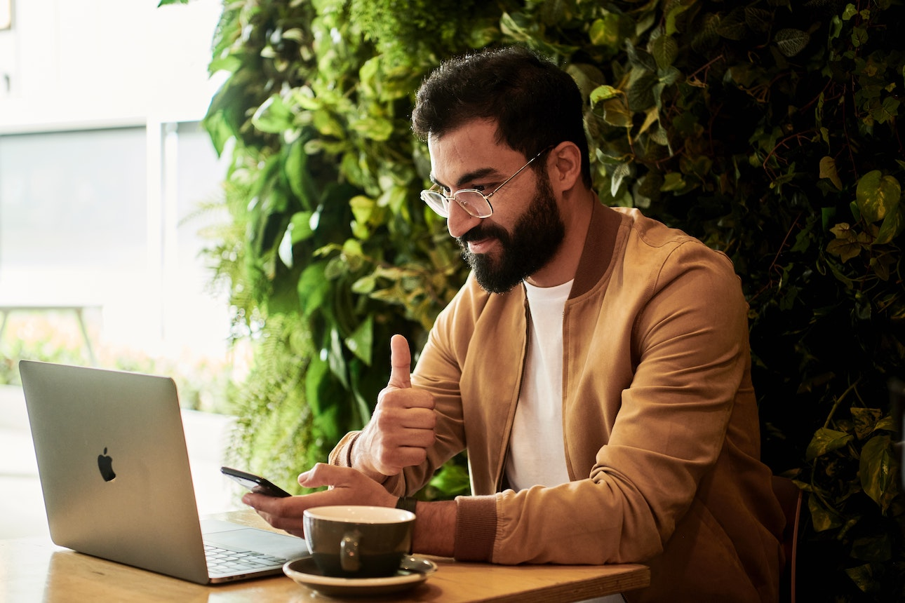 Man with beard holding a thumbs up in front of laptop and mobile phone, having a coffee