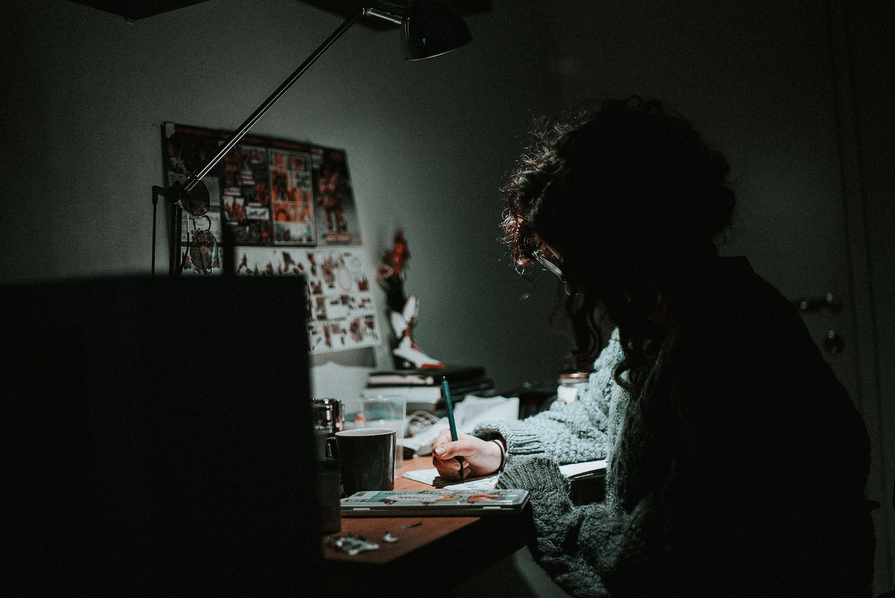 Woman with glasses writing with pen in the dark